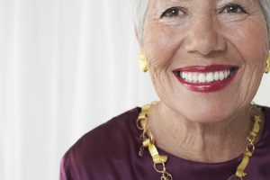 Closeup portrait of a smiling senior woman against white background